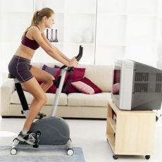 на рисунке женщина тренируется на тренажере для дома велосипед