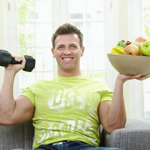 на фото мужчина с гантелей и тарелкой с овощами