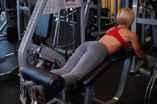 выполнять упражнение сгибание ног лежа на тренажере